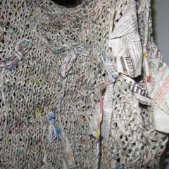 Kleid aus gerolltem Zeitungspapier gestrickt.