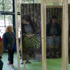 Besucherin neben einer Tapisserie von Andrea Milde